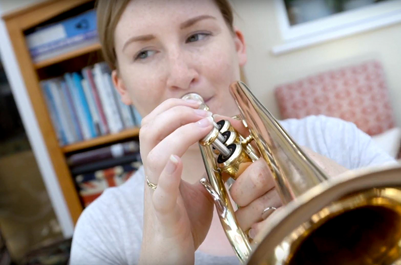 Careers in music: female army musician playing trumpet in rehearsal